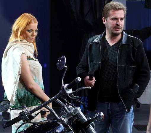 Стоцкая скептически смотрит на перспективу прокатиться по сцене за спиной Пономарева