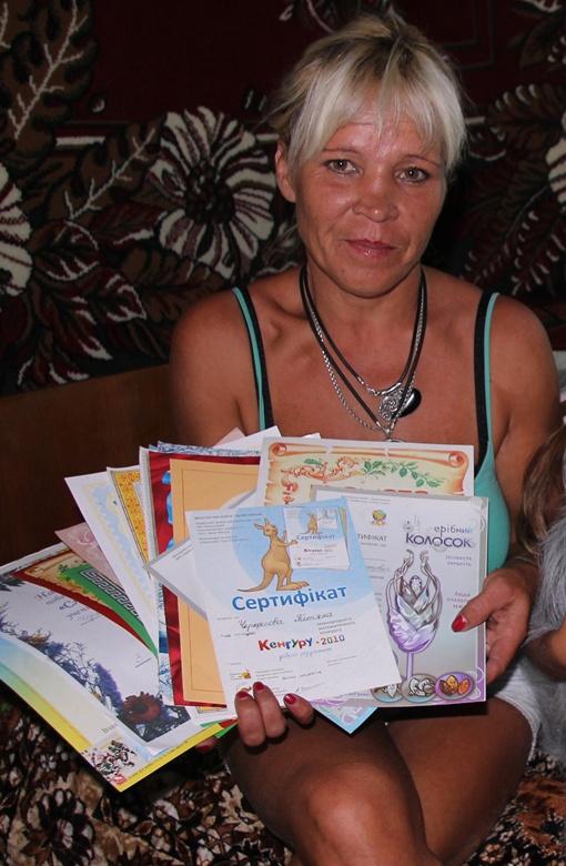 Танина мама показывает дочкины грамоты (всего около 20 штук!) за школьные олимпиады по разным предметам и соревнования по волейболу.